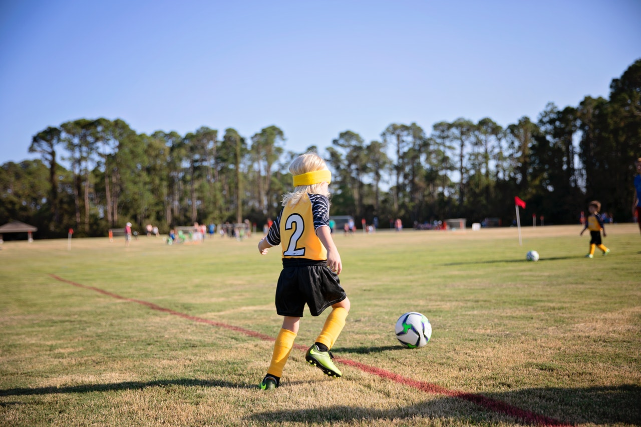 boy on field wearing yellow and white jersey
