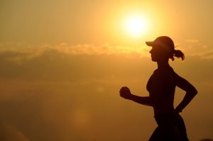 woman jogging with sun in the distance